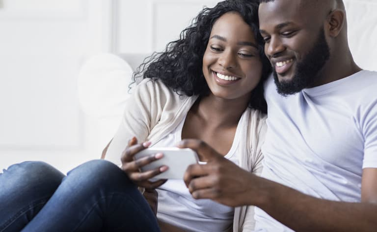 Young couple browsing social media on smartphone at home